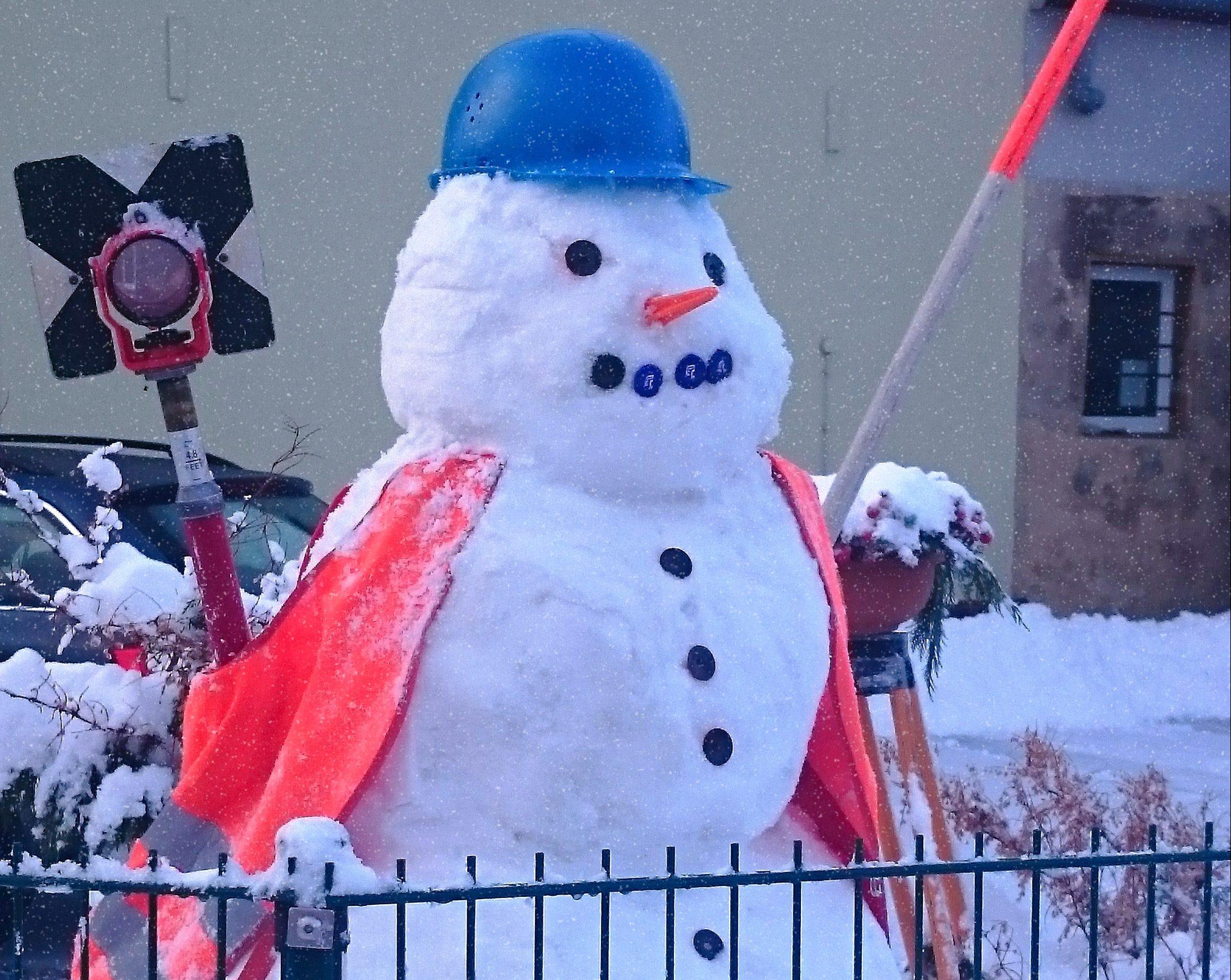 Schneemann mit Warnweste, Helm und Fluchtstange